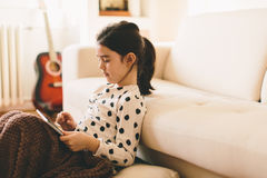 Little girl holding tablet in the room Stock Images