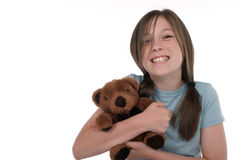Little Girl Holding Teddy Bear 8. Little girl with big, cheshire cat grin, smiling and sitting on floor holding a teddy bear. Shot on white royalty free stock image