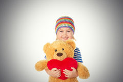 Little girl holding Teddy bear and heart. Royalty Free Stock Image