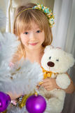 The little girl is holding a teddy bear in her hand near a white Stock Image