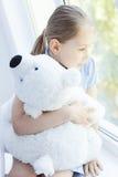 Little girl holding teddy bear Stock Images