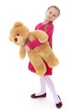 Little girl holding a teddy bear. Portrait in full Stock Image