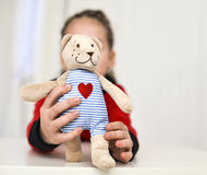 Little girl holding teddy bear sitting on the desk Stock Photography