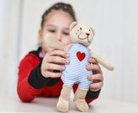Little girl holding teddy bear sitting on the desk Stock Photo