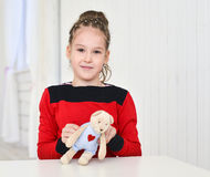 Little girl holding teddy bear sitting on the desk Royalty Free Stock Image
