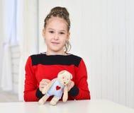 Little girl holding teddy bear sitting on the desk Royalty Free Stock Image