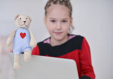 Little girl holding teddy bear sitting on the desk with laptop Stock Photos
