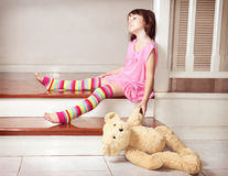 Little girl holding teddy bear. Little girl sitting on the porch and holding teddy bear Royalty Free Stock Photo