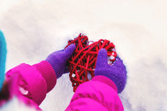 Little girl holding in their hands hearts themes Valentine`s day , the day of the winter on the street in the Park.  Stock Photos