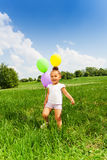 Little girl holding three flying balloons in park Royalty Free Stock Photography