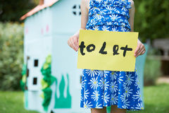 Little Girl Holding To Let Sign Outside Play House Royalty Free Stock Images