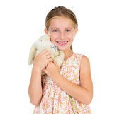 Little girl holding toy bunny with her eyes squinted Stock Image