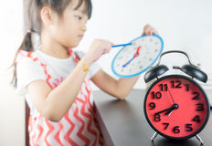 Little girl holding toy clock school time. Little asian girl holding toy clock school time Royalty Free Stock Photo