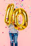 10th anniversary celebration party girl with golden balloons. Little girl holding two golden balloons making the 10 number while falling confetti on a pink Stock Photo