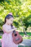 Little girl holding ukulele in park Stock Photography