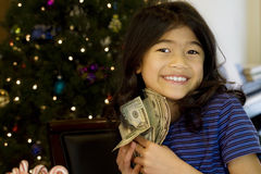 Little girl holding up cash Stock Image