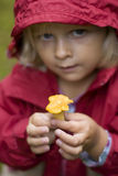 Little girl holding up a mushroom. A little girl dressed in a rain coat is holding up a small yellow chanterelle Stock Images