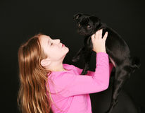 Little girl holding up puppy. Cute little girl holding black pug puppy Royalty Free Stock Images