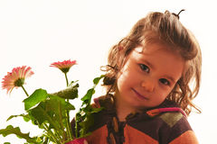 Little girl holding vase with flowers. Portrait of a beautiful little girl holding vase with flowers looking at the camera smileing on white background Stock Photography