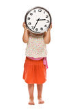 Little girl holding a wall clock in his hand Stock Photos