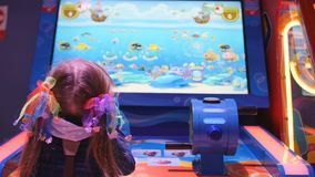 Little girl holding water gun and playing the virtual shooting game with water gun on playground in trade mall. In 4K stock footage