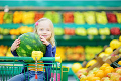 Little girl holding a watermelon in a food store or a supermarket Stock Photos