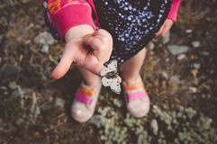 Little Girl Holding White Butterfly. Photo looks down at bottom half of a small child holding a white butterfly on her index finger royalty free stock photo