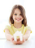 Little girl holding white paper house. Home and family concept - little girl holding white paper house Royalty Free Stock Images