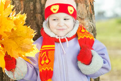 Little girl holding yellow with gold autumn leaves bunch in hand outdoor portrait Royalty Free Stock Photo