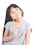 Little girl holding yellow pencil, thinking Stock Images