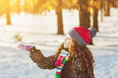 Little girl holding young green plant in winter forest. Ecology Royalty Free Stock Images