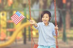 Little girl holds American flag in the playground Royalty Free Stock Photo