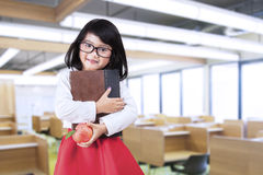 Little girl holds a book and apple. Cheerful little girl standing in class while holding a book and apple Royalty Free Stock Photo