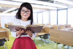 Little girl holds book in reading room Royalty Free Stock Photo