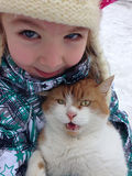 Little girl holds a cat in winter weather Stock Image
