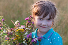 Little girl holds flowers and smiles in dry field at summer Stock Photos
