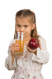 Little Girl Holds a Glass with an Apple Juice with One Hand and Royalty Free Stock Photos