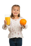 Little Girl Holds a Glass with an Orange Juice wit Stock Photography