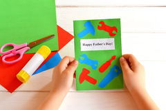 Little girl holds greeting card in hands. Happy father's day. Children's paper crafts. Kids art idea. Fathers day gift. Kids crafts for fathers day. Fathers day Stock Photography
