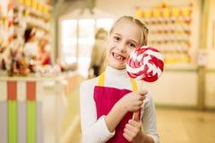 Little girl holds handmade sugar caramel on stick. Happy little girl holds handmade sugar caramel on stick. Fresh lollipop in candy store Stock Image