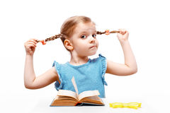 Little girl holds with hands the braids so far sits at a table. white background. isolate. The little girl dressed in a blue t-shirt with strips holds with Royalty Free Stock Photo