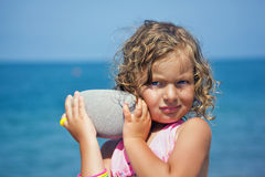 Little girl holds in hands pebble on seacoast Royalty Free Stock Photography