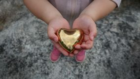 A little girl holds a heart of gold Royalty Free Stock Photos
