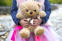 Little girl holds her teddy bear. Doll Royalty Free Stock Images