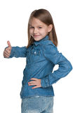 Little girl holds her thumb up and looks back Royalty Free Stock Image