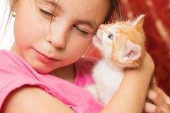 A little girl holds a kitten in her arms and hugs. stock photo