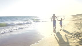 Little girl holds mother's hand. As they skip through the surf and then past camera.Shot on Canon 5D Mk2 at at a frame rate of 30 fps stock video footage