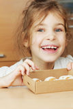 Little girl holds open box of corrugated cardboard with cookies Stock Photo