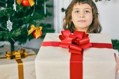 Cheerful cute little child girl with present. Kid holds a gift box near Christmas tree indoors. Stock Image