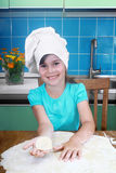 Little girl holds on palm piece of dough Stock Image